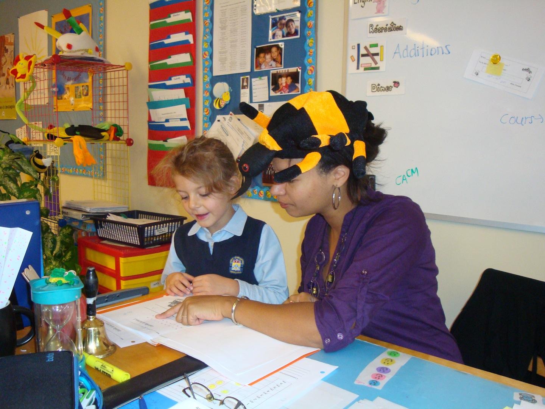 Madame Josiane travaillant avec une élève. C'est bien la classe des abeilles!